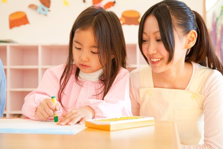 schooling: Kindergarten girls enjoy drawing and kindergarten teacher watches