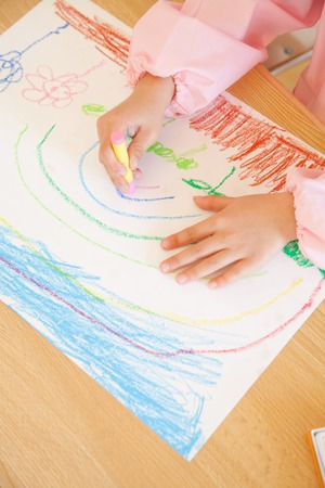 kindy: Kindergarten girls draw pictures with crayons in hand Stock Photo