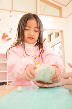 smocking: Kindergarten girl playing with clay Stock Photo