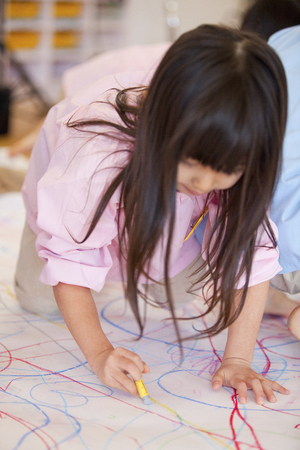 reggio emilia: Kindergarten girls draw pictures on parchment paper