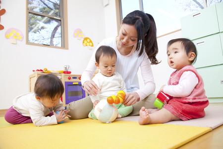 maestra enseñando: Juega con juguetes guardería y jardín de infantes Foto de archivo