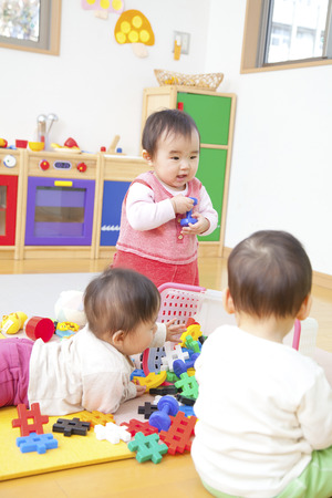 Nursery school children play with toys
