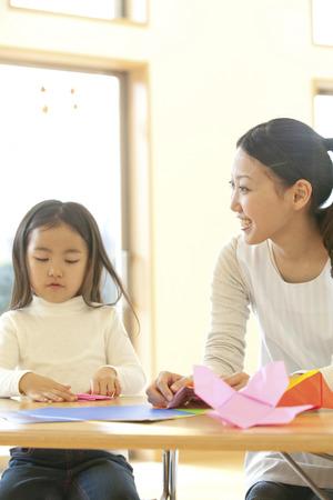 kindy: Nursery and preschool girls folding origami Stock Photo