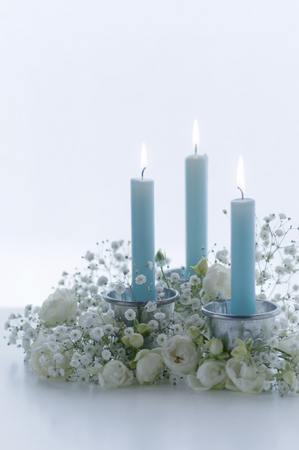 blue candles: White flowers of flower arrangement and blue candles Stock Photo