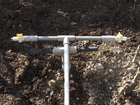flowerbed: Flowerbed watering pipe Stock Photo