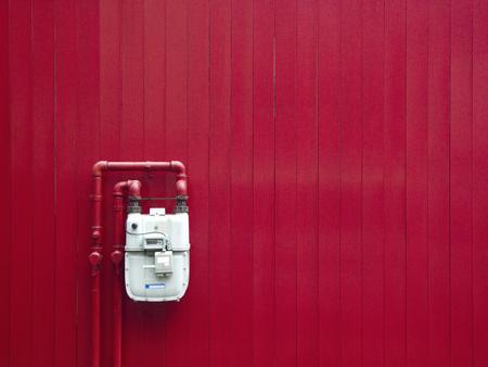 赤い壁の都市ガスのメーター 写真素材