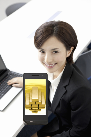 net worth: Gold bullion to OL and mobile screen Stock Photo