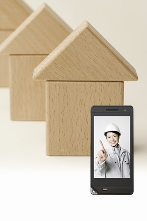 Person wearing work clothes, which goes to the building blocks and the portable screen of the house Stock Photo