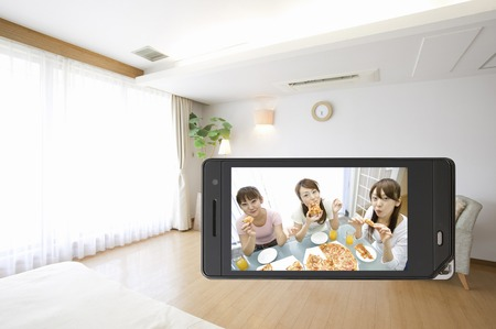 family and friends: Three women of to eat at home, which moves to the mobile screen Stock Photo