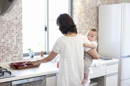 母は台所に立って、赤ん坊を保持