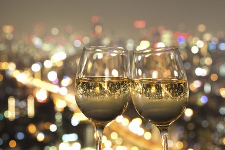 Nacht uitzicht van de stad weerspiegeld in het glas wijn Stockfoto