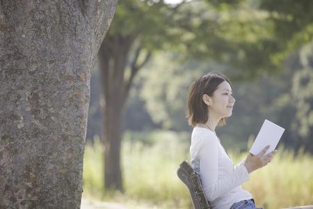 los seres vivos: Mujer que lee un libro que se sienta en el banquillo Foto de archivo