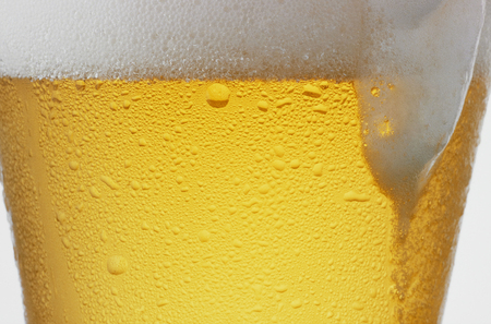 sizzle: Foam and beer of sizzle that flows down from the glass