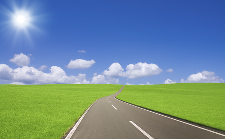 gleam: Grasslands road with clouds and Sun Stock Photo