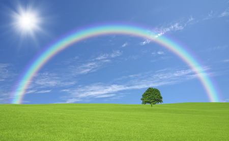 Ippongi meadow with clouds and Sun and Rainbow Stock Photo