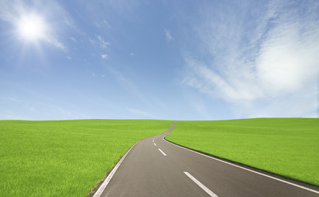 grasslands: Grasslands road with clouds and Sun Stock Photo