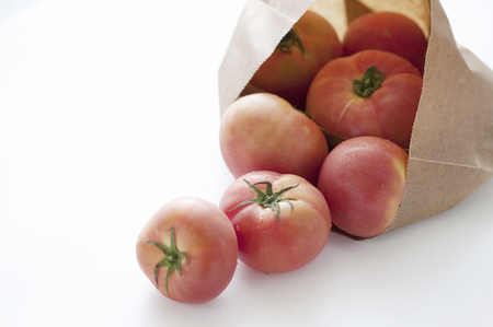 roll out: Tomatoes roll out from the bag Stock Photo