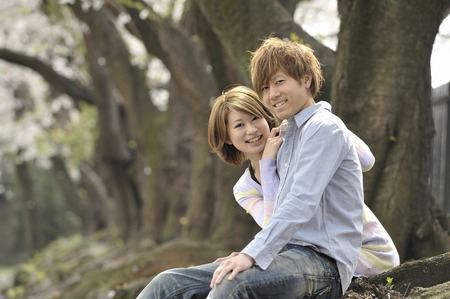 feel affection: A couple cuddling under a cherry tree Stock Photo