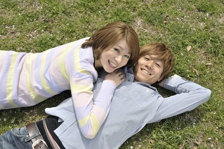 feel affection: Young couple to lie down on the grass