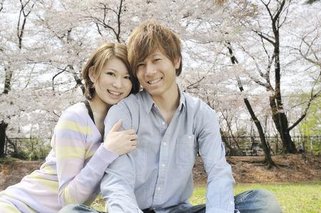A couple cuddling under a cherry tree 写真素材