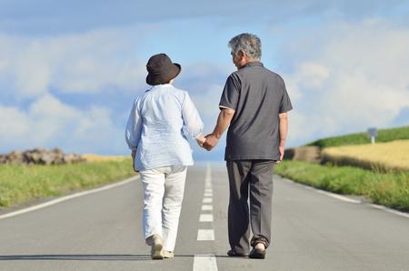 年配のカップルが手をつないで一つの道を歩く