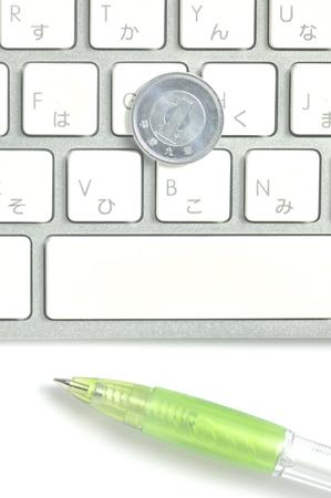 ballpoint pen: Keyboard and one yen coin and ballpoint pen Stock Photo