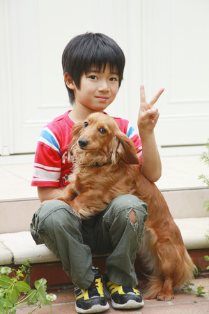 red tshirt: Pets and boy wearing a red T-shirt play Stock Photo