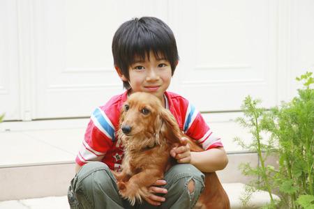 ペットと少年の身に着けている赤い t シャツの再生 写真素材