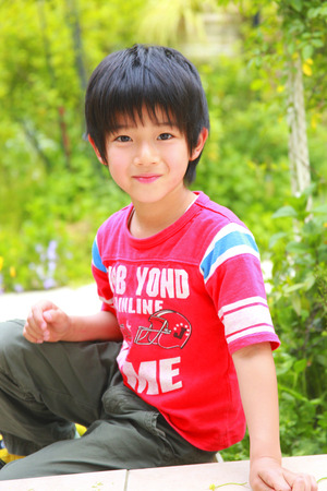 kindergartener: Boy wearing a red shirt playing in the garden