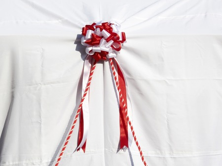 unveiling: White curtain and the red and white ribbon of the monument unveiling Stock Photo