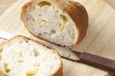 pan frances: Corte el pan francés con un cuchillo. Foto de archivo