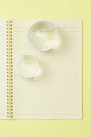空白のノートブックとクリスタルの地球儀