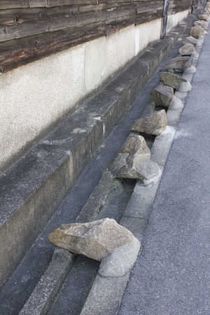 nuisance: Handicap stones to avoid the nuisance parking placed along the fence of the Japanese house Stock Photo