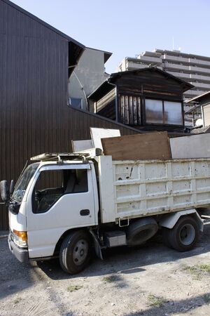 tenement: Truck loaded with scrap wood after renovation the tenement house