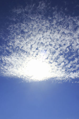 gaping: Gaping floating white clouds and sun in the autumn sky Stock Photo