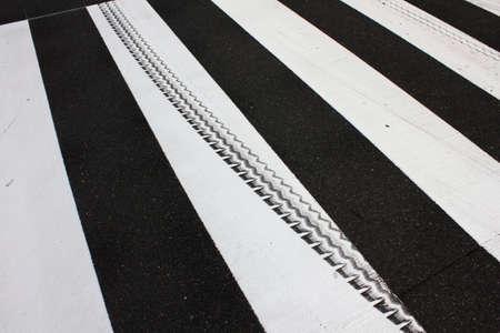 paso de cebra: Marcas del neumático de la línea blanca del paso de peatones