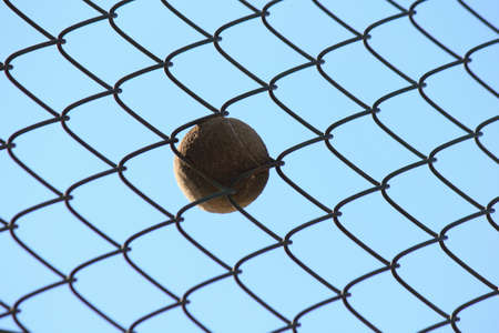 into: Tennis ball that cuts into the wire mesh Stock Photo