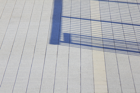 The shadow of the iron fence that reflected in the banks of the floor tile 写真素材