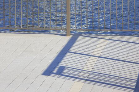 iron fence: The shadow of the iron fence that reflected in the banks of the floor tile Stock Photo
