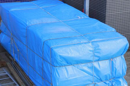 tarpaulin: Luggage covered in blue sheet