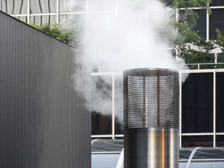 vapore acqueo: Chimney to issue the water vapor from the building of the basement boiler room Archivio Fotografico