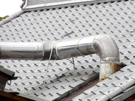 penetrate: Flue gas duct to penetrate the house of roof tiles Stock Photo