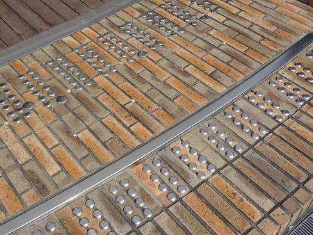 braille: Braille panels stuck on the sidewalk bricks