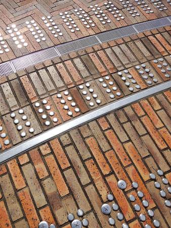 braile: Paneles Braille atrapados en los ladrillos de la acera
