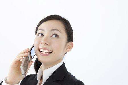 携帯電話で会話する OL