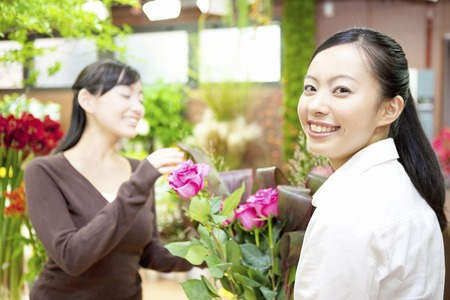 store clerk: Store clerk with a bouquet Stock Photo