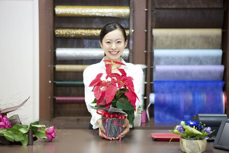 store clerk: Female store clerk with a Poinsettia