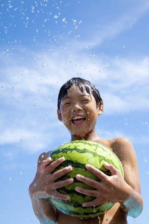 スイカに臨む子供たちの夏 写真素材