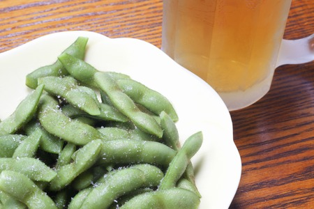 entered: Beer that entered the edamame and mug Stock Photo