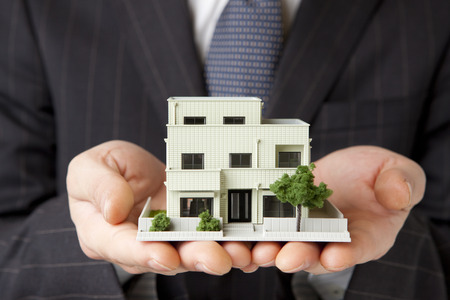 building safety: Businessman with a model House